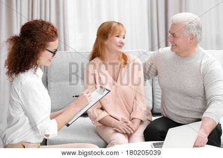 Middle aged couple signing contract sitting on couch at home
