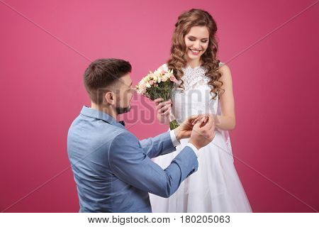 Happy wedding couple on color background