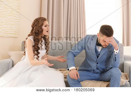 Young couple quarreling at home on wedding day