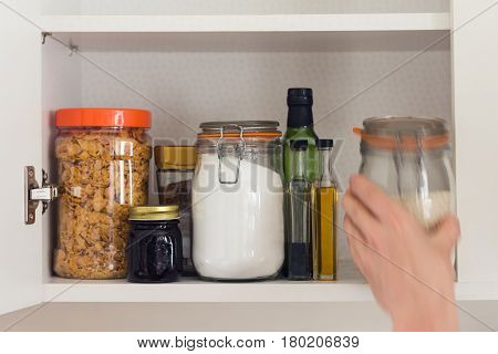 jars and containers of cereals jam coffee sugar flour oil vinegar rice in pantry