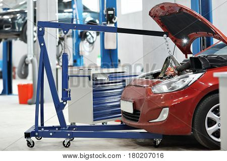 automobile mechanic a crane removed the engine from the car. repairing auto in automobile store.