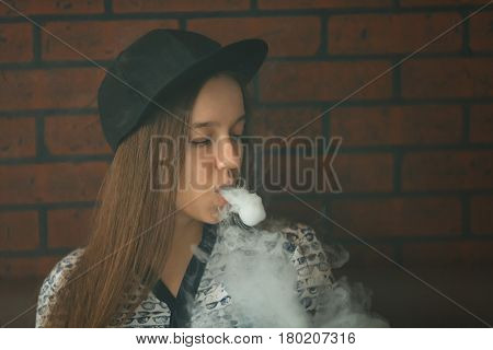 Vape. Young Handsome White Girl In A Cap Is Admiting Puffs Of Steam From The Electronic Cigarette. V