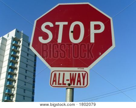 All Way Stop Sign With Apartment Building And Blue Sky