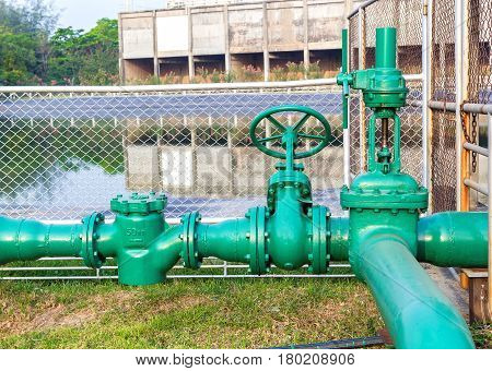 Large green water valve that controls the opening and closing of the reservoir.