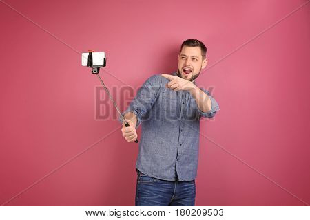 Young man taking selfie on color background