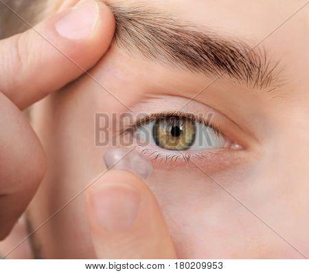 Young man putting contact lens, closeup