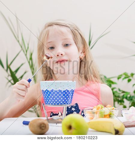 Little girl preparing and eating a chocolate fondue. Chocolate fondue with kiwi banana apple tangerine and marshmallow. Happy little girl.
