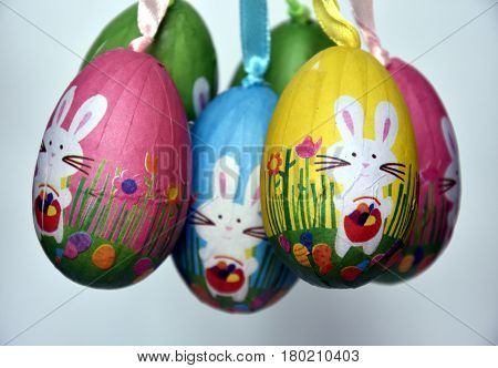 Bunch of colourful panted plastic eggs with white bunnies. Easter or Paschal eggs are used as gifts. Easter Bunny (Easter Rabbit or Hare) is a folkloric figure and symbol of Easter.