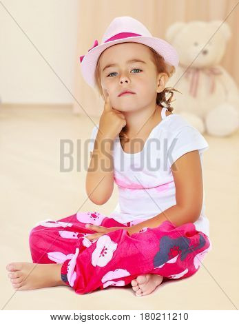 Brooding a little, tanned girl in the pink hat sits on the floor, folding his Turkish legs. Girl keeps the index finger in front of their face.In the children's room in which sits a Teddy bear.