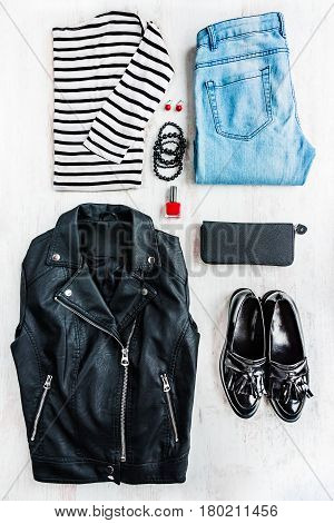 Urban style woman collage clothing. Top view of a leather jacket striped blouse jeans and accessories.