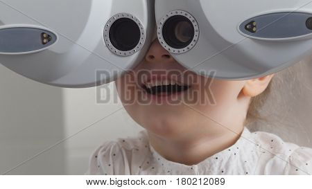 Ophthalmology clinic - adorable little blonde girl checks vision eyesight, close up, telephoto