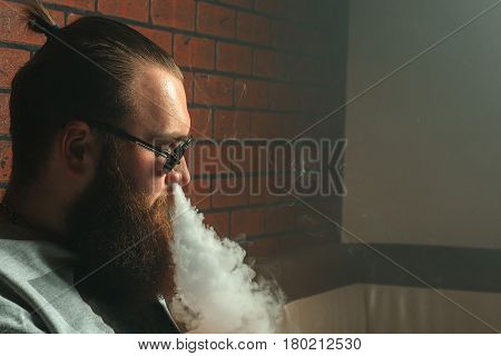 Vape. Young Brutal White Guy With Large Beard And In Sunglasses Is Admiting Puffs Of Steam From The