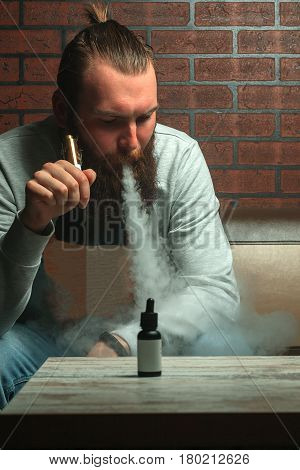 Vape. Young Brutal White Guy With Large Beard Is Admiting Puffs Of Steam From The Electronic Cigaret