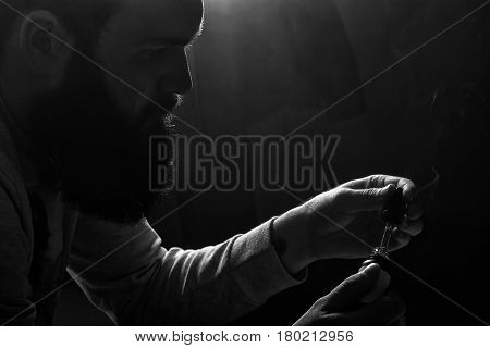Vape. Young Brutal White Guy With A Bottle Of E-liquid For Electronic Cigarette. Black And White Pho