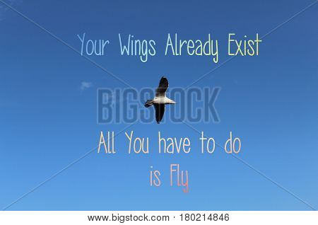 Inspirational text on blue sky with lone bird flying in clear sky. Conceptual image. Your wings already exist. All you have to do is fly.