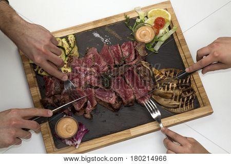 Couple eating grilled T-bone sliced beef steak and vegetables.People eating beef steak.