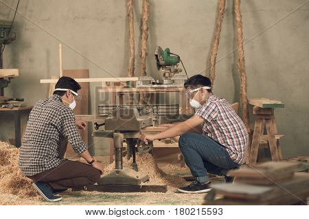 Father and son in masks and goggles using bend saw in workshop