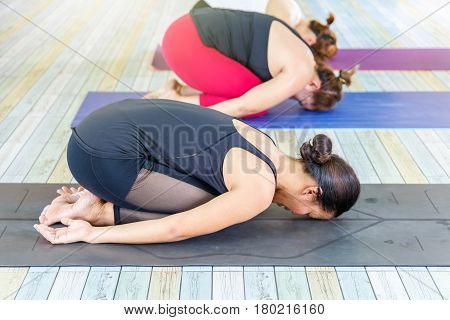 Group of young asians woman practicing during their yoga class in a gym