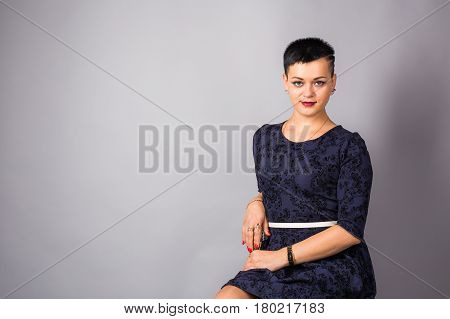 Pretty short haired woman in blue dress.