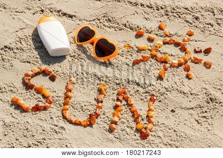 Word And Shape Of Sun, Sunglasses With Sun Lotion On Sand At Beach, Summer Time