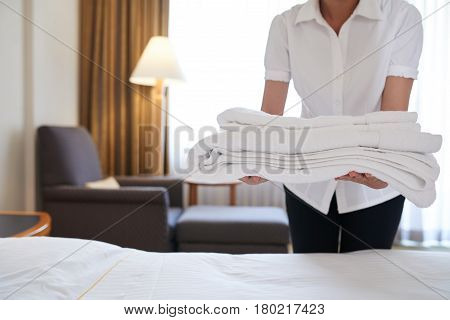 Hotel maid bringing fresh towels to the room