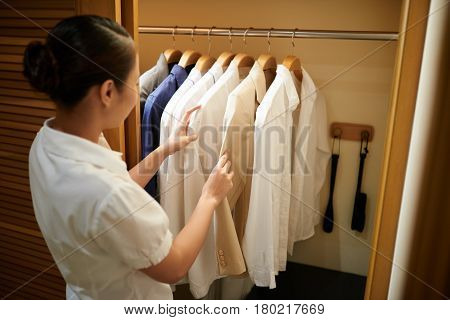 Chambermaid checking clothes in closet of guest