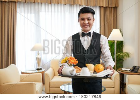 Smiling Vietnamese waiter bringing breakfast to the hotel room