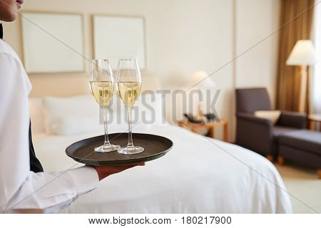 Water bringing tray with two glasses of champagne to the room