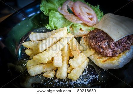 Close-up of burger,meat,onion,potato fries,cheese & with and green salad on a set table.Famous fastfood around the world