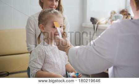 Cute blonde girl with mommy in child's ophthalmology - optometrist diagnosis eyesight, close up