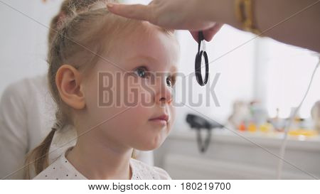 Cute child in ophthalmology clinic - optometrist diagnosis little blonde girl, close up