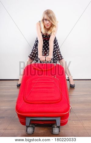Traveling vacation concept. Elegant young woman in full length wearing polka dot black dress pulling heavy red travel bag