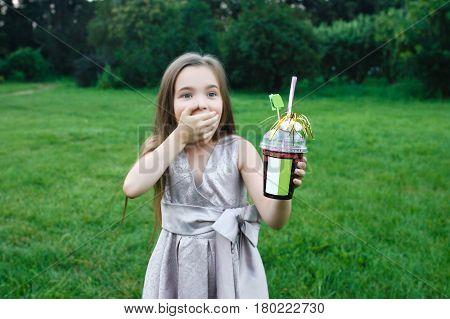 Little cute girl walks alone in a meadow and drinks juice