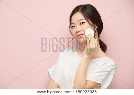 Lovely Korean woman applying toner on her skin