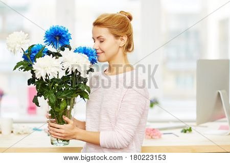 Profile view of attractive young woman sniffing blue chrysanthemum with closed eyes while standing in spacious design studio