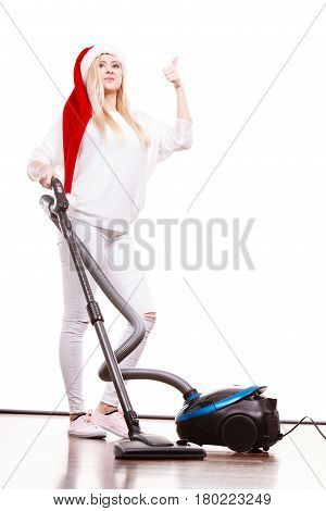 Woman vacuuming the house. Funny teen girl in santa helper hat with vacuum cleaner giving thumb up hand sign gesture. Christmas time and housework concept.