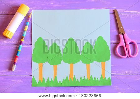 Creating Earth day card. Step. Guide. Earth day card with trees and grass, scissors, glue stick, pencil, template, paper sheets on a wooden table. Earth day paper crafts project for kids. Top view