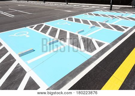 Road marking for handicapped parking stall in a parking lot