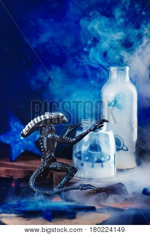 Dark space themed still life with stars, alien, UFO and mystical smoke