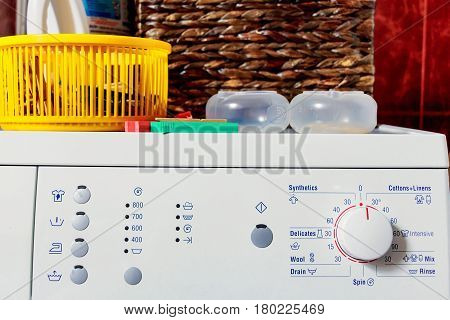 Close up top of modern washing machine in bathroom with facilities on it: cleanser, colorful plastic containers and pegs