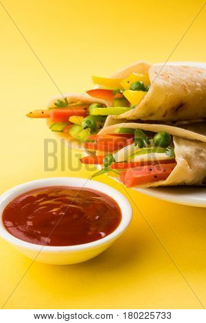 Indian popular street food called veg franky made using vegetables wrapped inside paratha/chapati/roti with tomato ketchup
