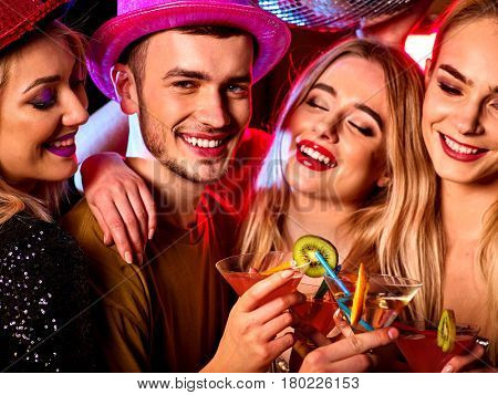Cocktail party with group people dancing and drink cocktail. Women and men have fun in night club. Happy couple with alcohol drink on foreground and disco ball on background.