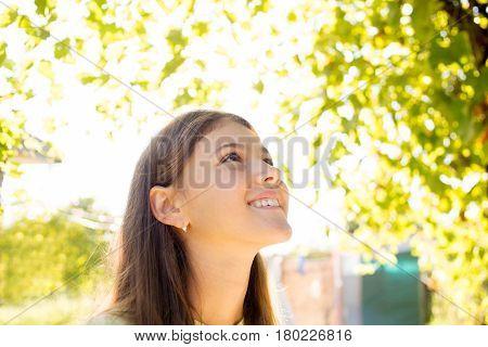 Smiling little girl in enjoying sunshine light feeling happiness.Fun and harmony in sunshine light.
