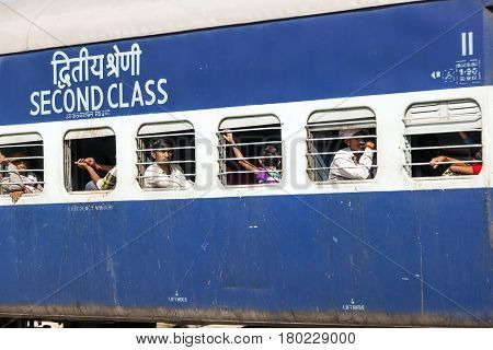 JAIPUR INDIA - OCTOBER 23: Unidentified passengers hanging at the window of a moving Indian Railway train on October 232012 in Jaipur India. Indian Railways carries about 7500 million passengers annually.