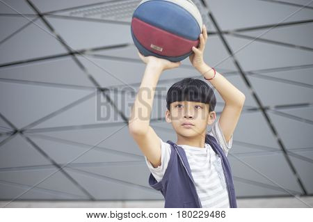 Portrait Of Cool Asian Kid Holding Basketball Outdoors