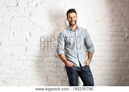 Happy young goodlooking caucasian man in casual outfit standing at white brick wall, plenty of copyspace.