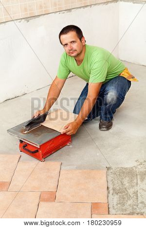 Man cutting ceramic floor tiles with electric cutter - laying flooring in a new building