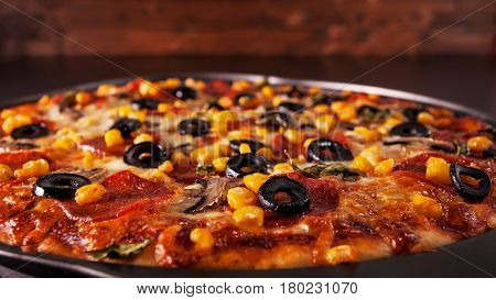 Freshly baked delicious pizza in baking pan - closeup with copy space above low key