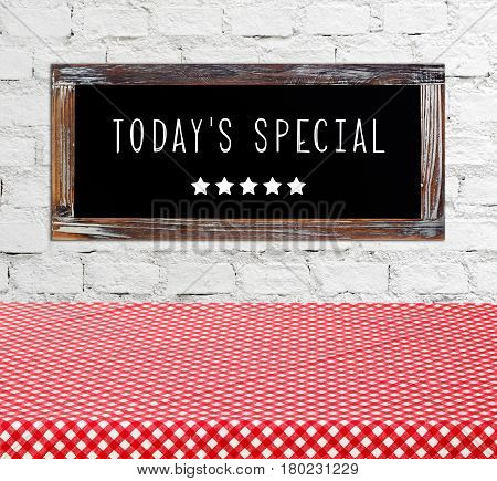 Today's special on vintage chalk board over empty table covered with red check tablecloth food and dinks background food display montage