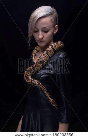 Woman in leather dress with python on black background